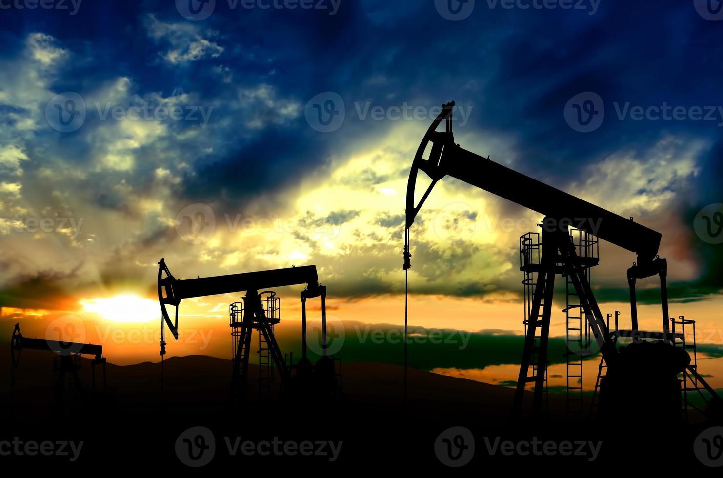 pompes à huile travaillant sur fond de coucher de soleil photo