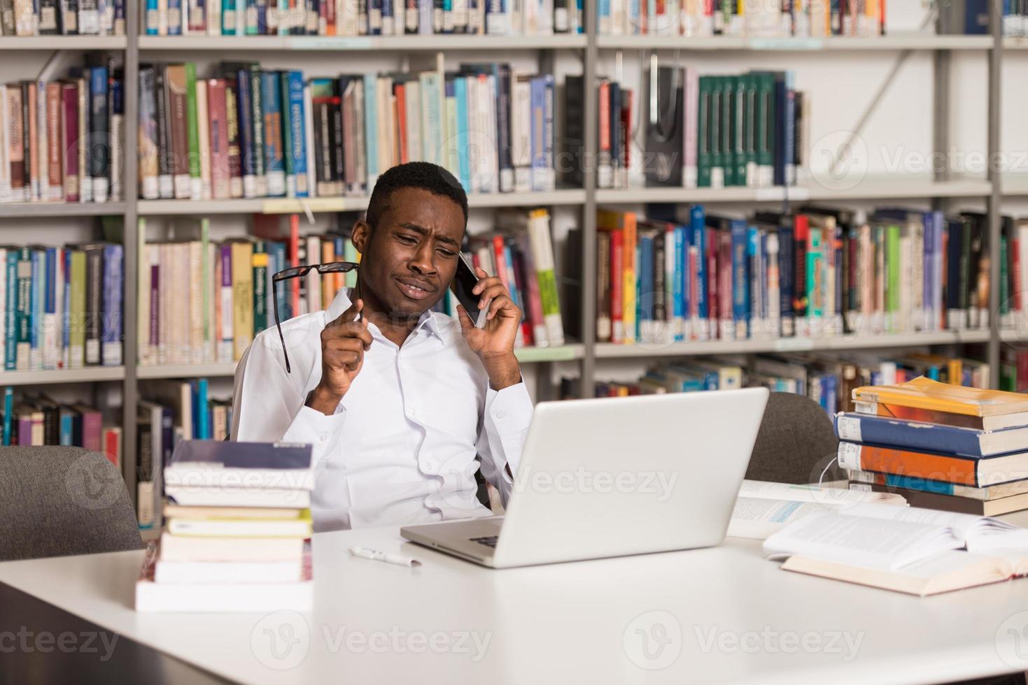 étudiant masculin, parler téléphone, dans, bibliothèque photo