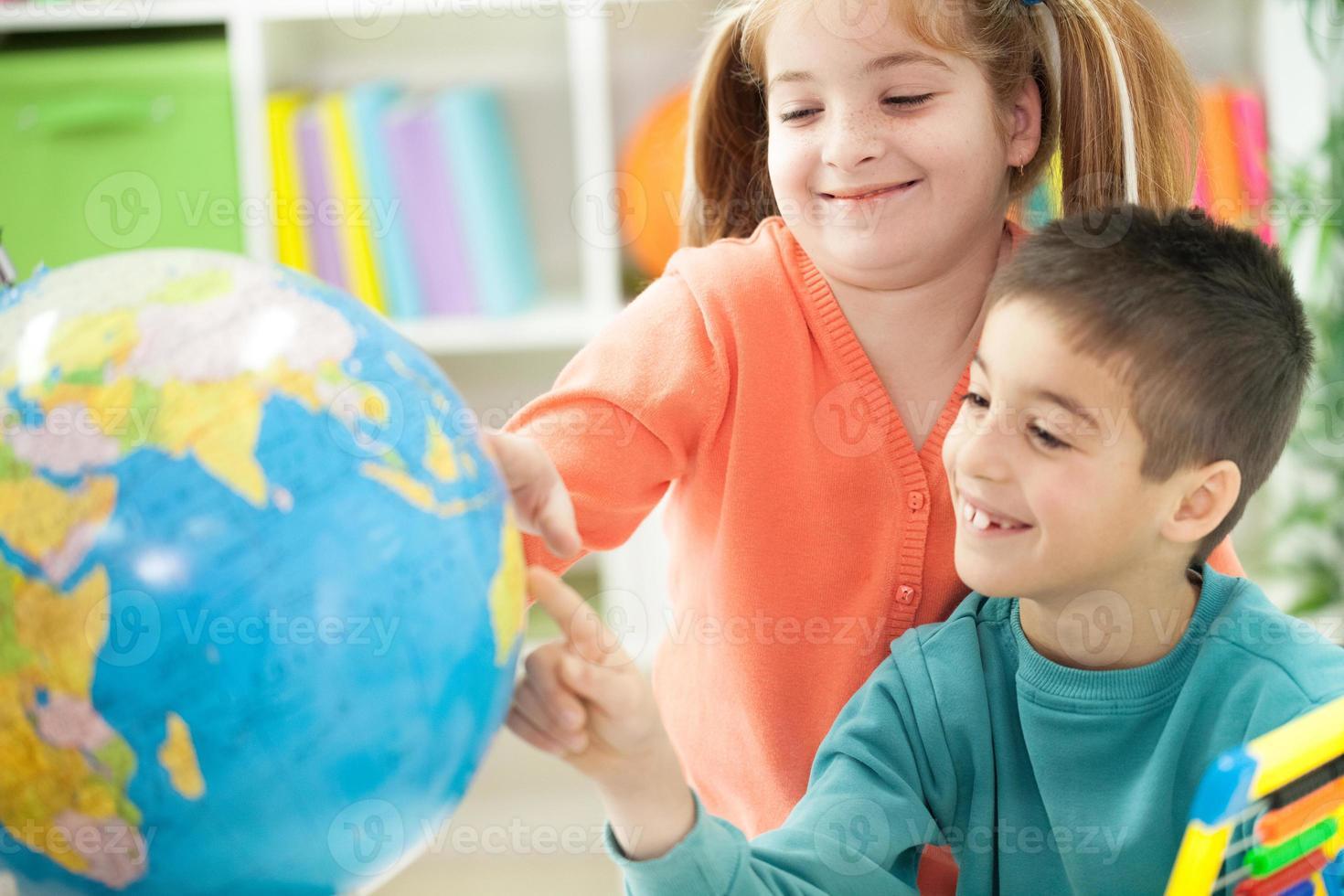 jeune frère sœur montre la place sur le globe photo