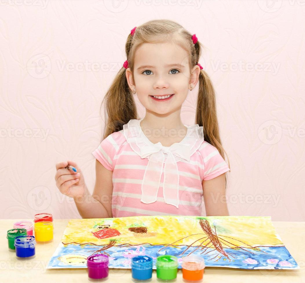 mignonne petite fille souriante dessin avec de la peinture et un pinceau photo