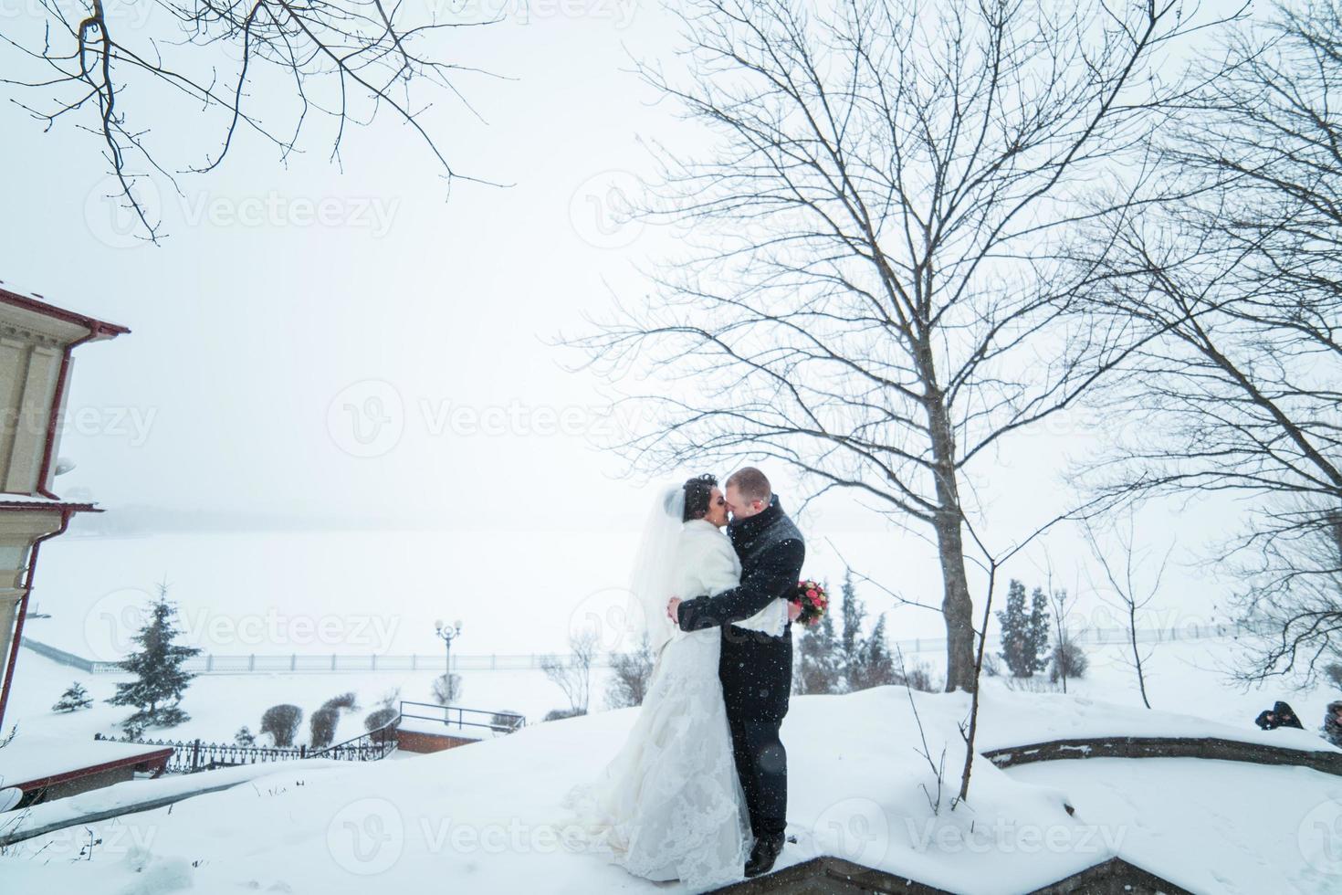 mariée et le marié marchant sur la ville dans la neige photo