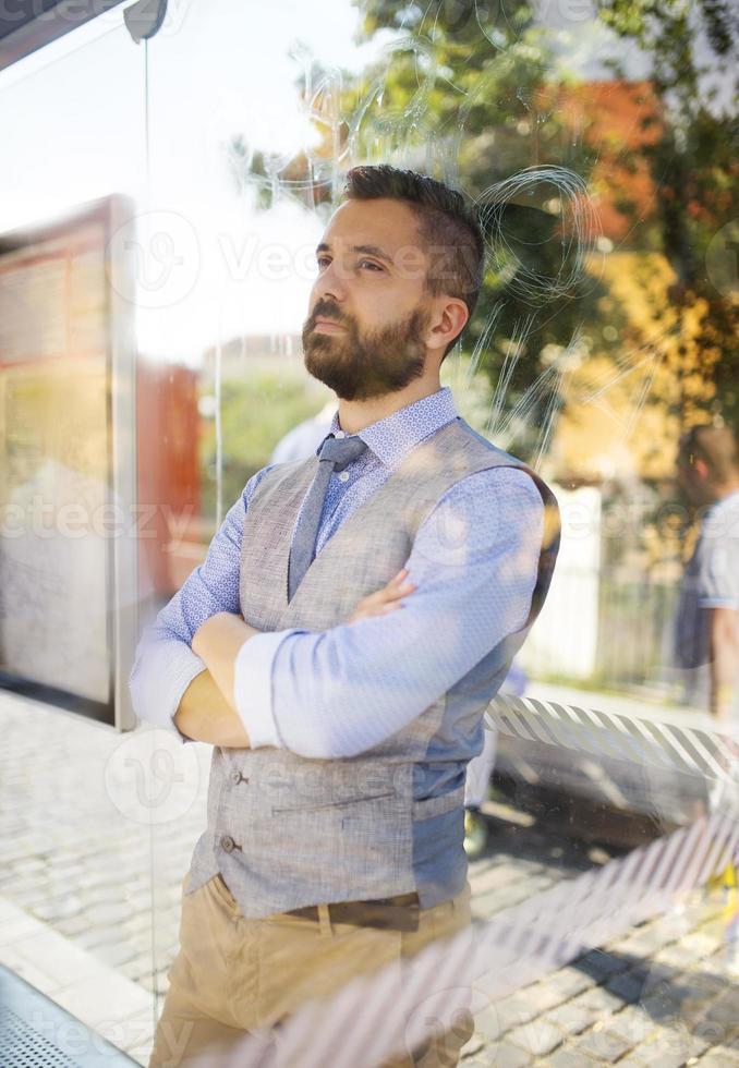 homme d'affaires hipster en attente de bus photo