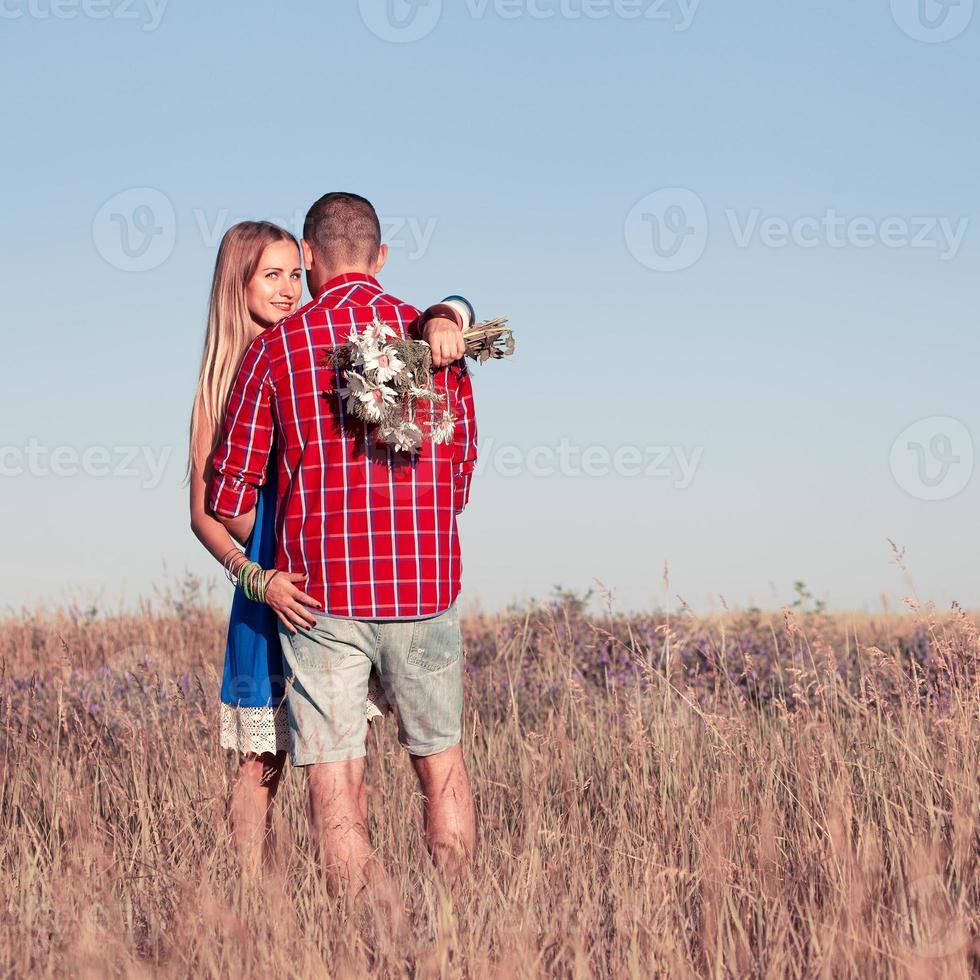 histoire d'amour. beau jeune couple marchant dans le pré, en plein air photo