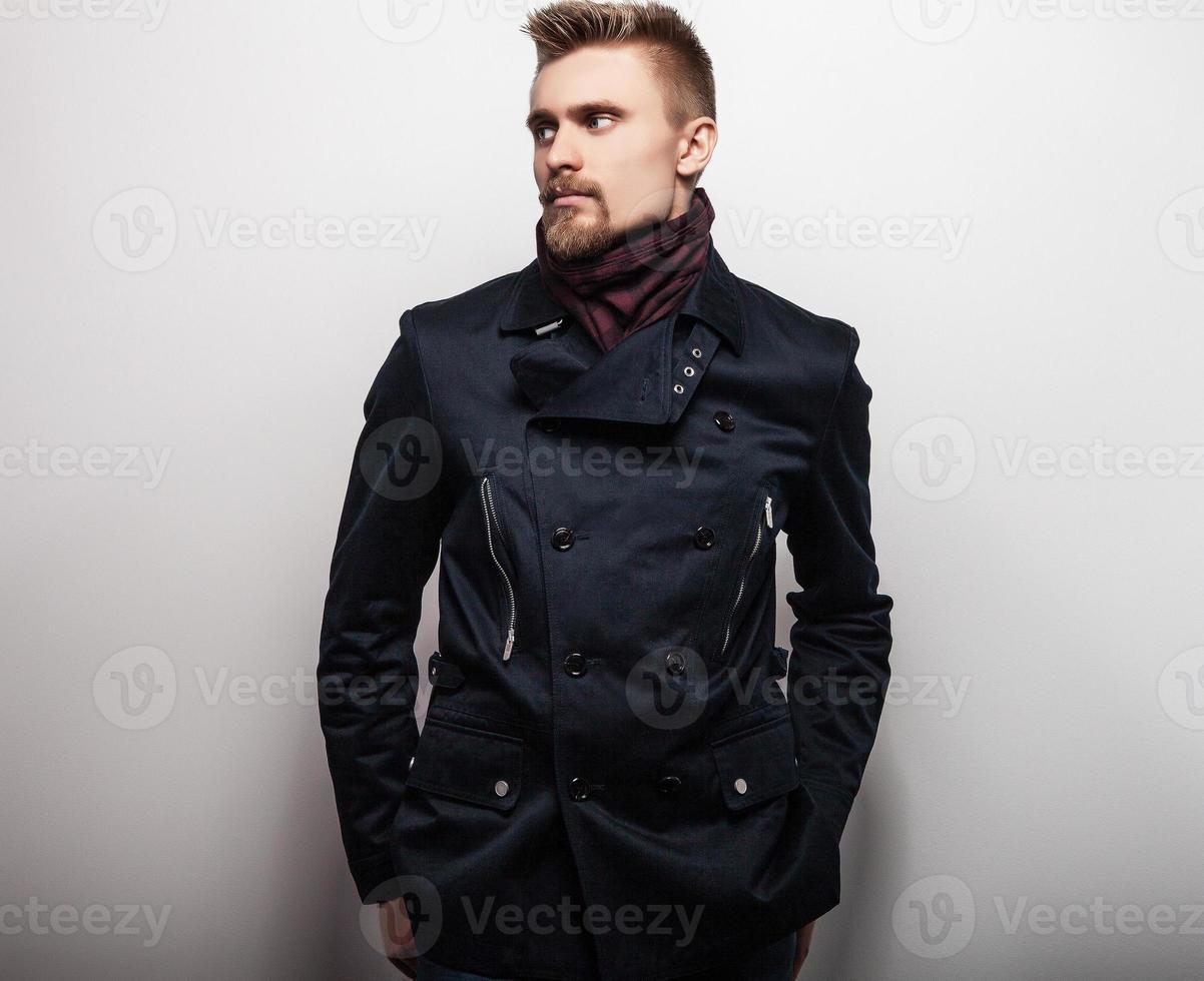 élégant jeune bel homme en manteau noir. portrait de mode studio. photo