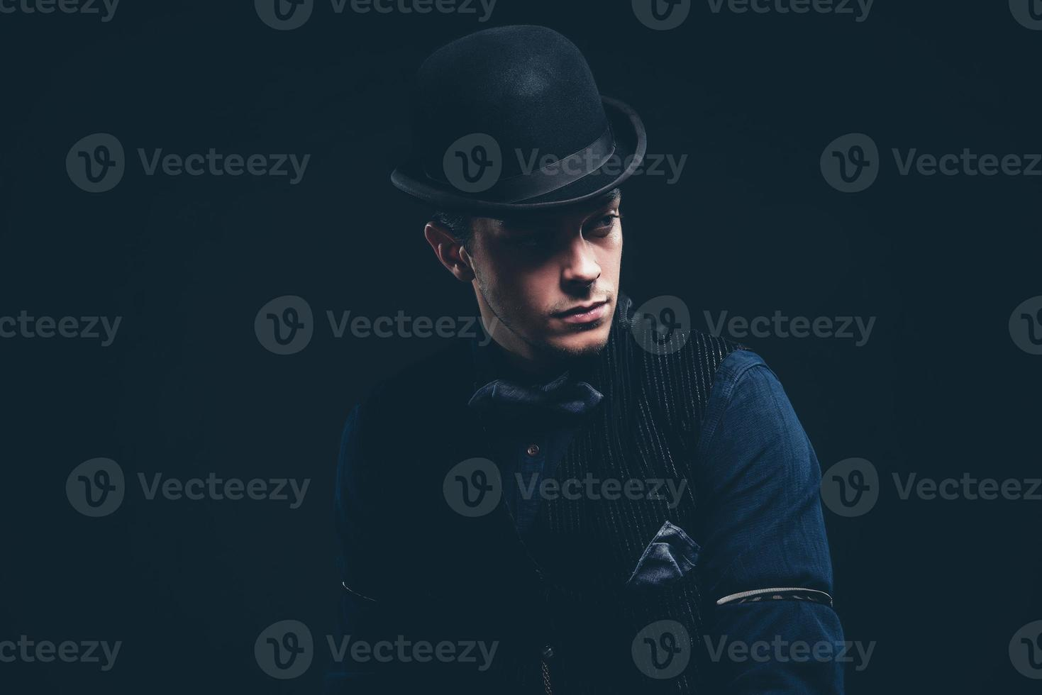 homme de mode vintage avec chemise bleue, gilet, jeans, noeud papillon. photo
