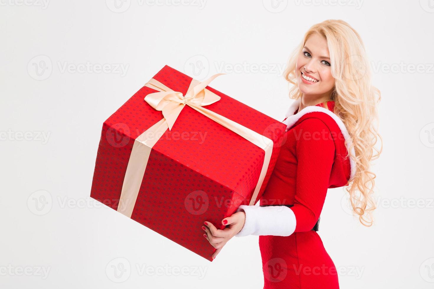 femme joyeuse dans des vêtements du père Noël tenant un gros cadeau rouge photo