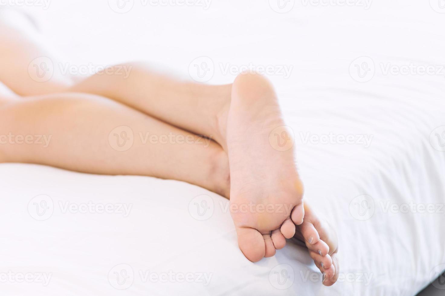 jeune femme, coucher lit, à, closeup, de, pieds nus photo
