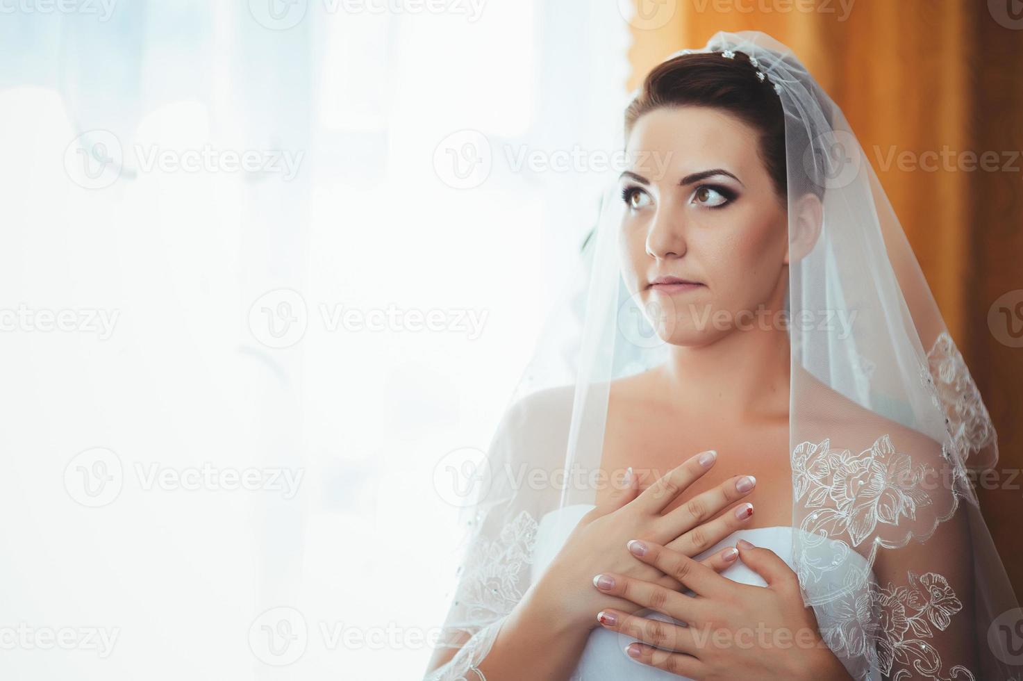 belle mariée se prépare en robe de mariée blanche avec coiffure photo