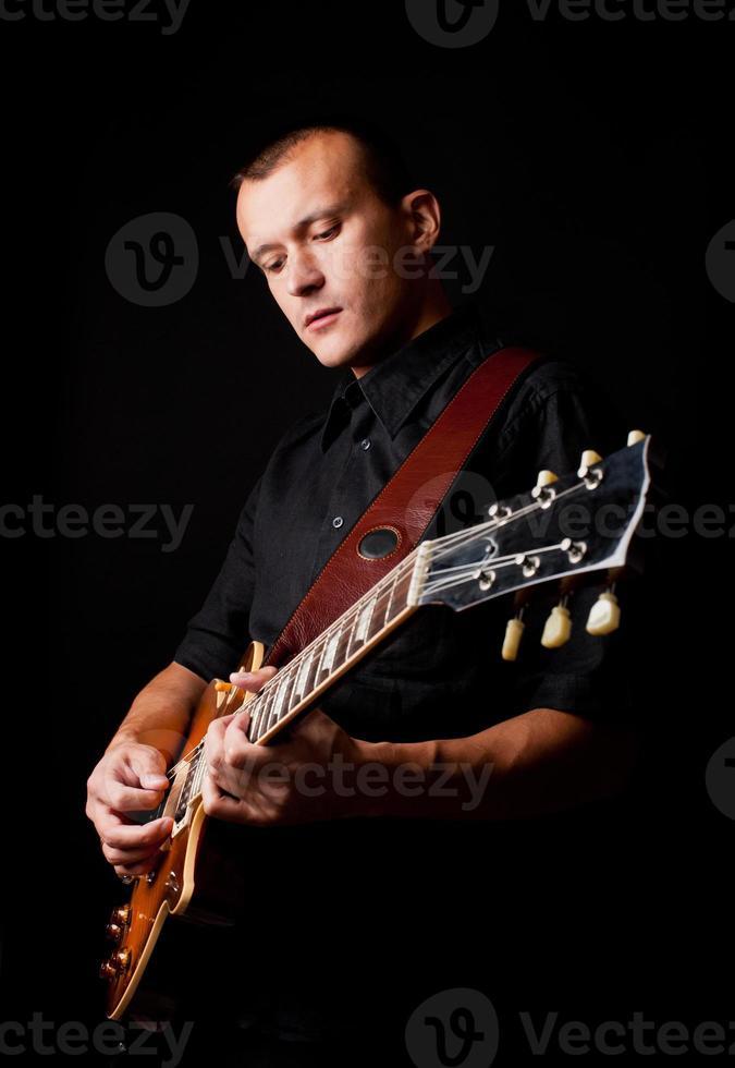 beau jeune homme jouant de la guitare photo