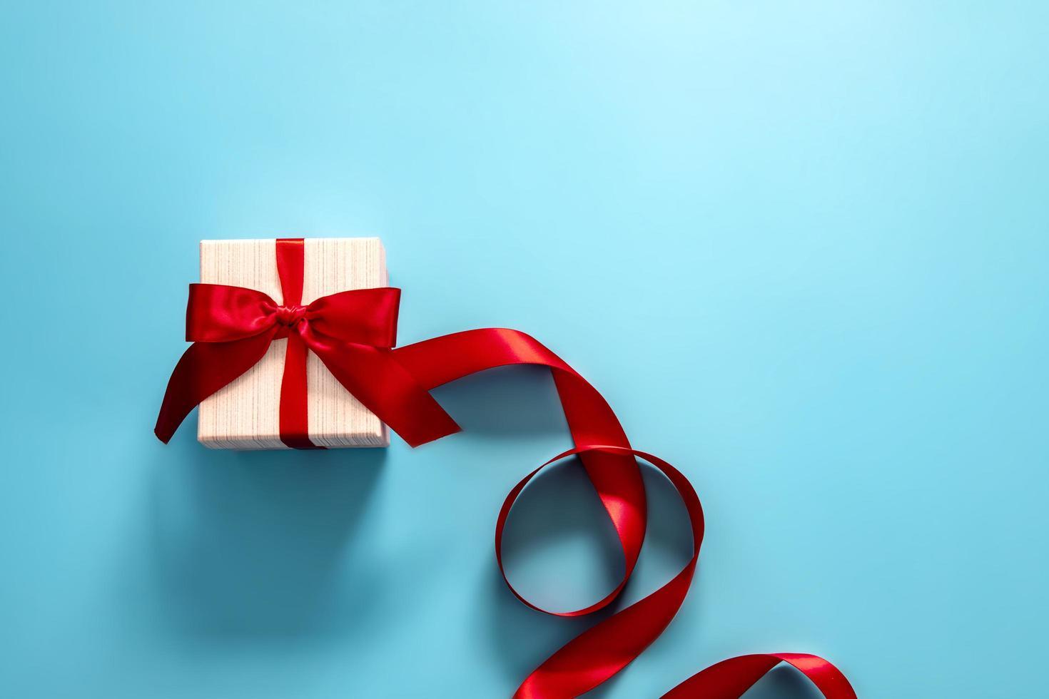 coffret cadeau avec ruban rouge sur fond bleu photo
