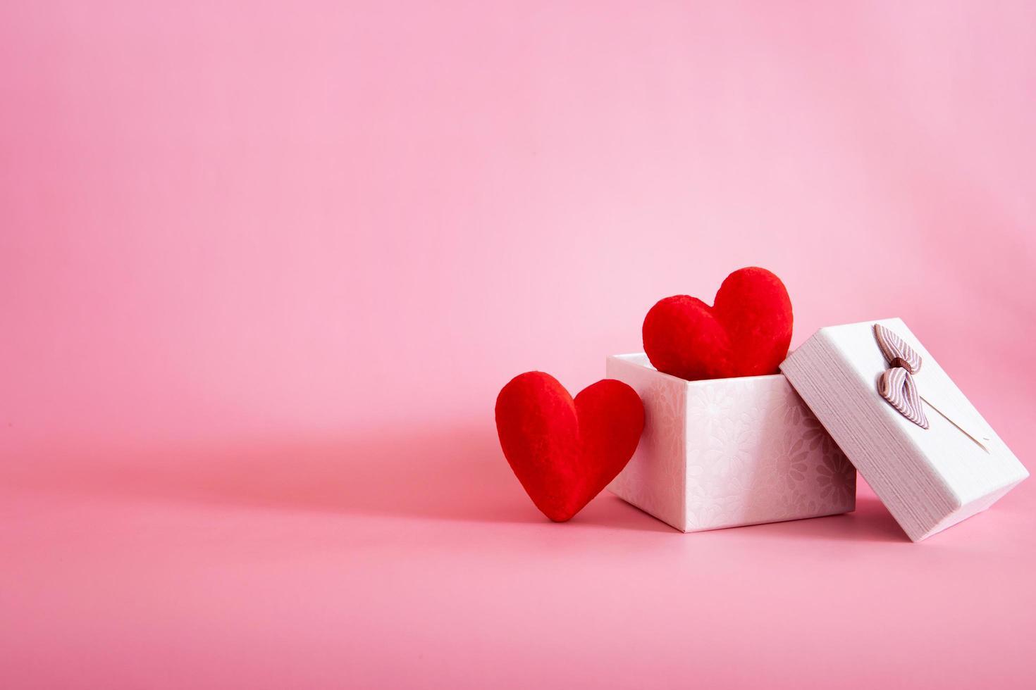 deux coeurs rouges dans une boîte cadeau sur fond rose photo