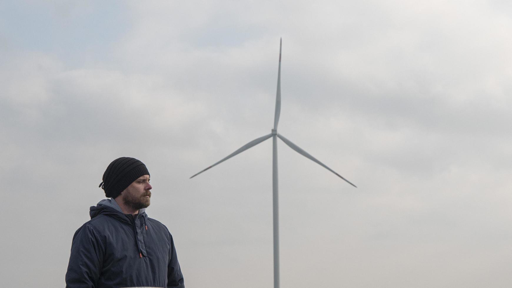 l'homme se dresse sur fond de moulin à vent photo