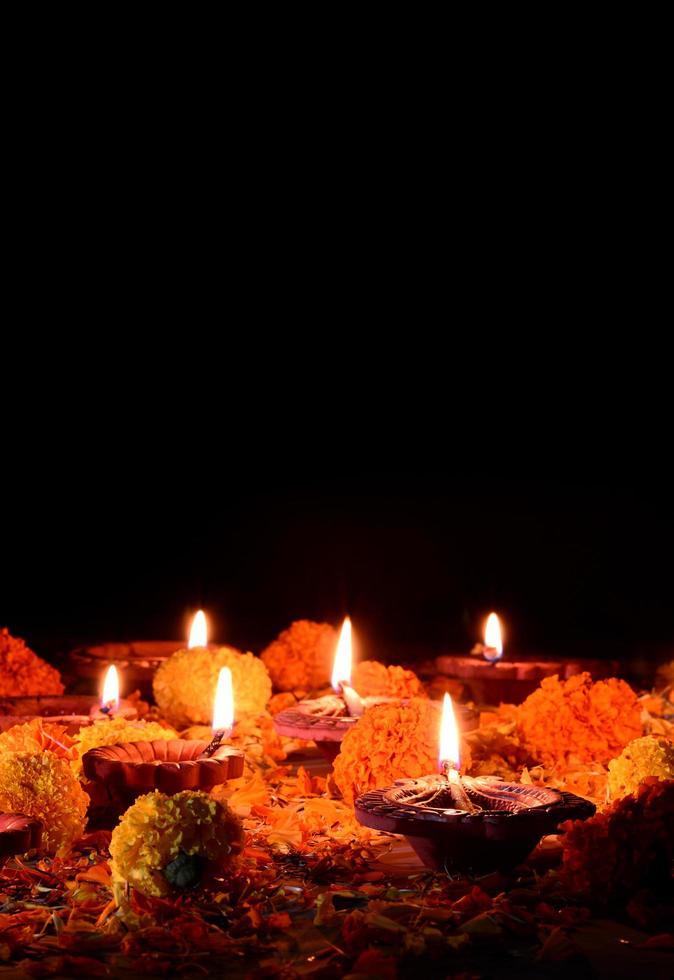 lampes diya en argile éclairent un fond noir pendant la célébration de diwali photo