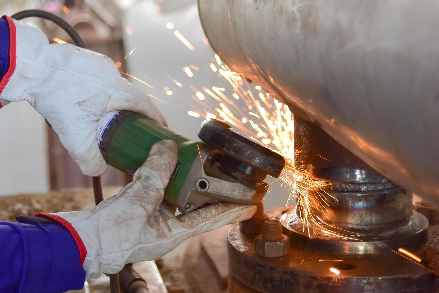 travailleur moud un tuyau en acier photo