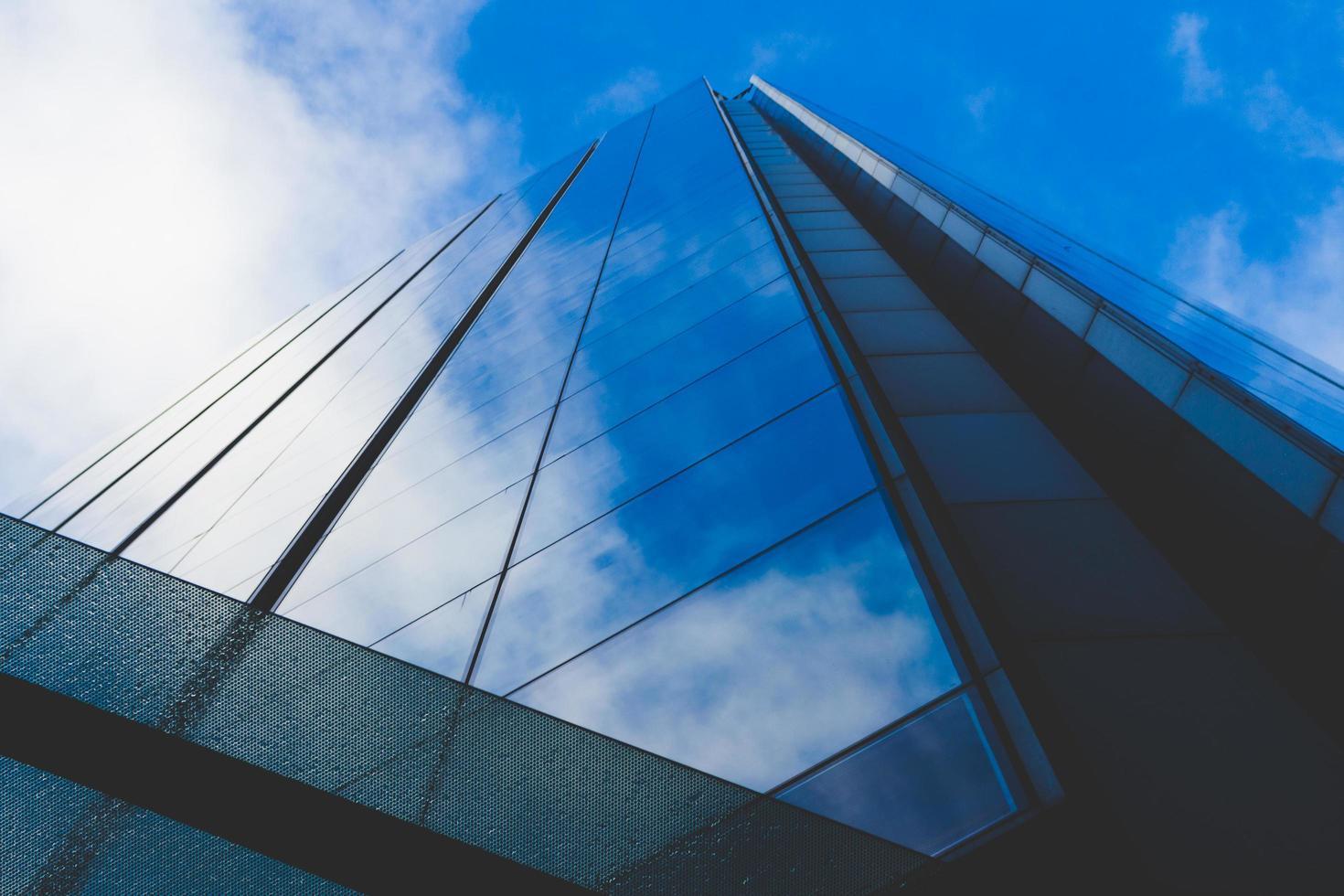 nuages et ciel bleu se reflétant dans les fenêtres du bâtiment photo