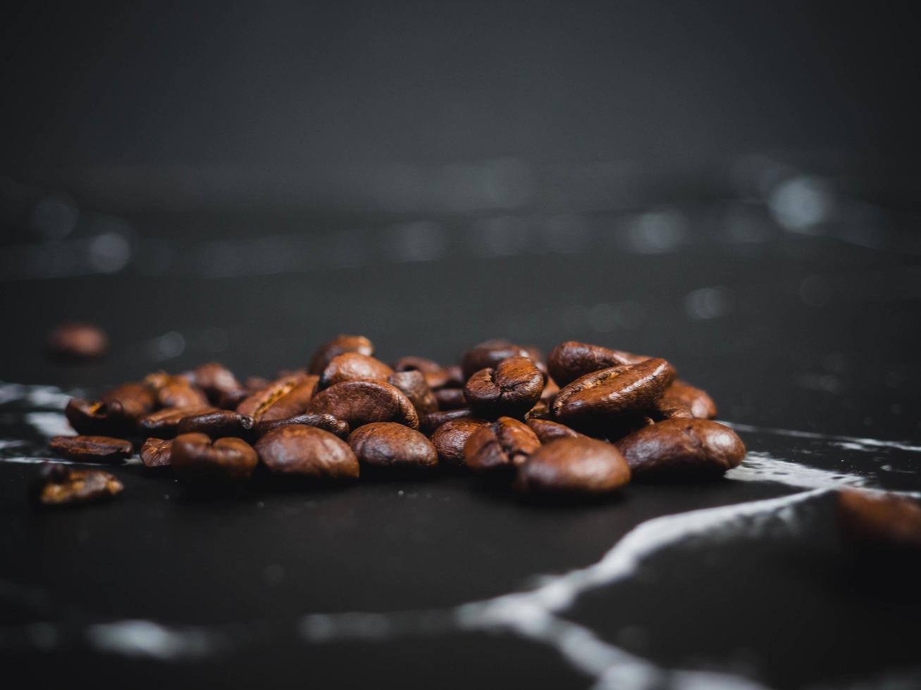 grains de café sur une surface en marbre noir photo