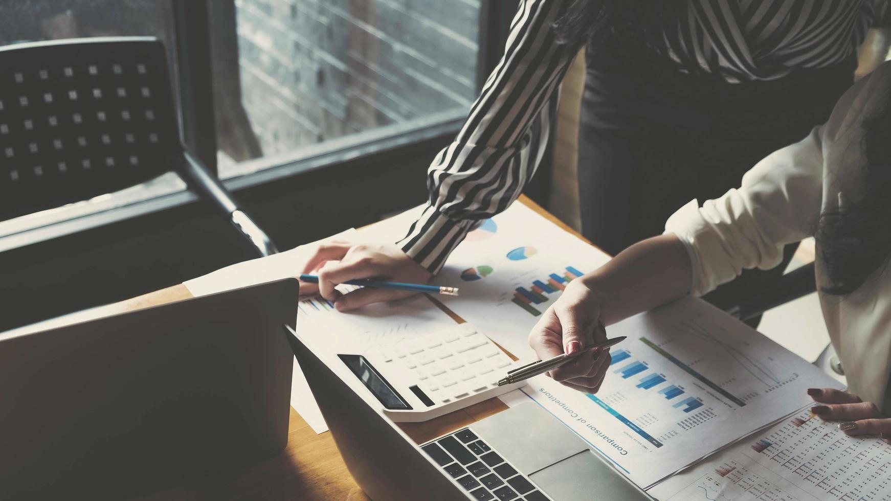 deux femmes d'affaires analysant les graphiques et travaillant sur ordinateur portable photo