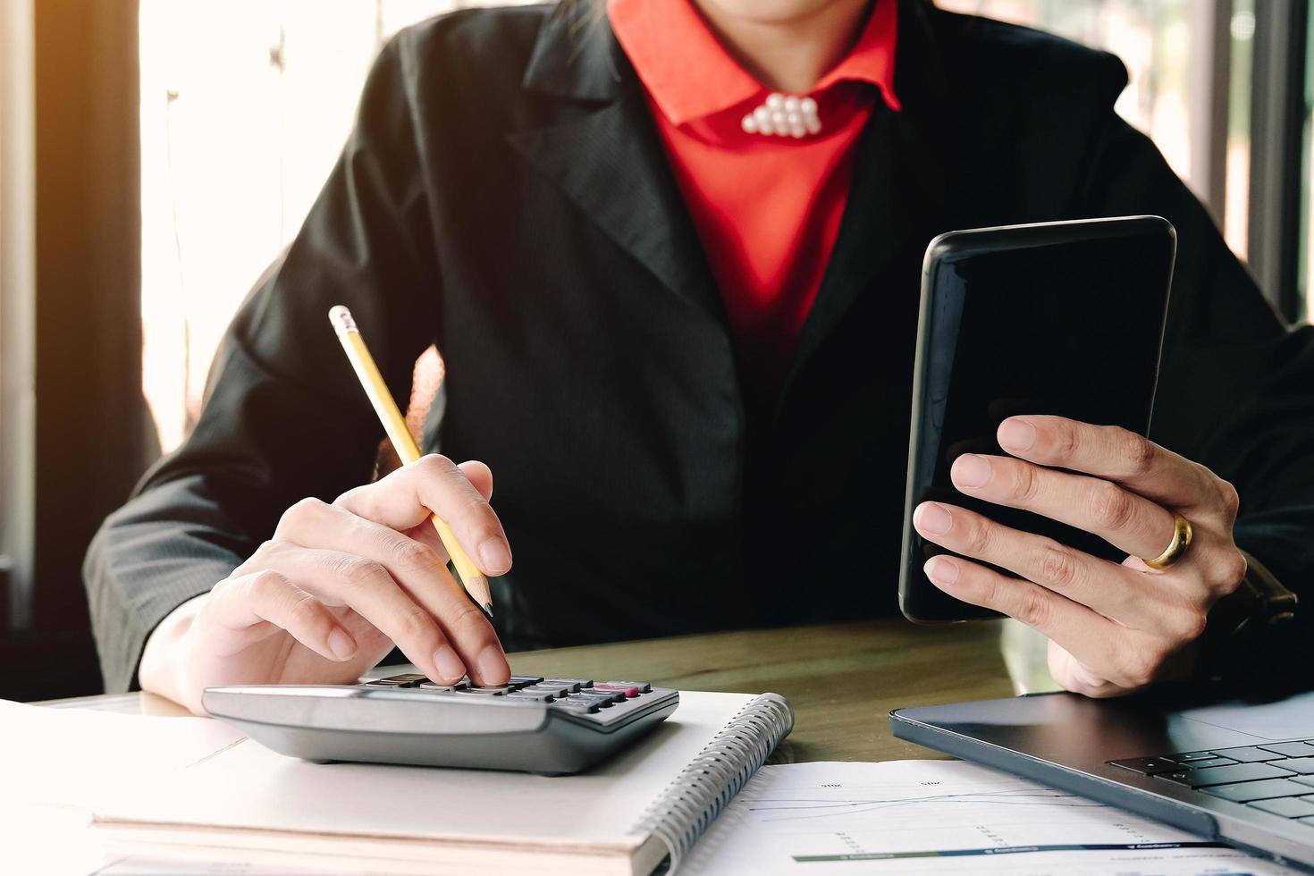 femme affaires, regarder, smartphone, utilisation, calculatrice photo