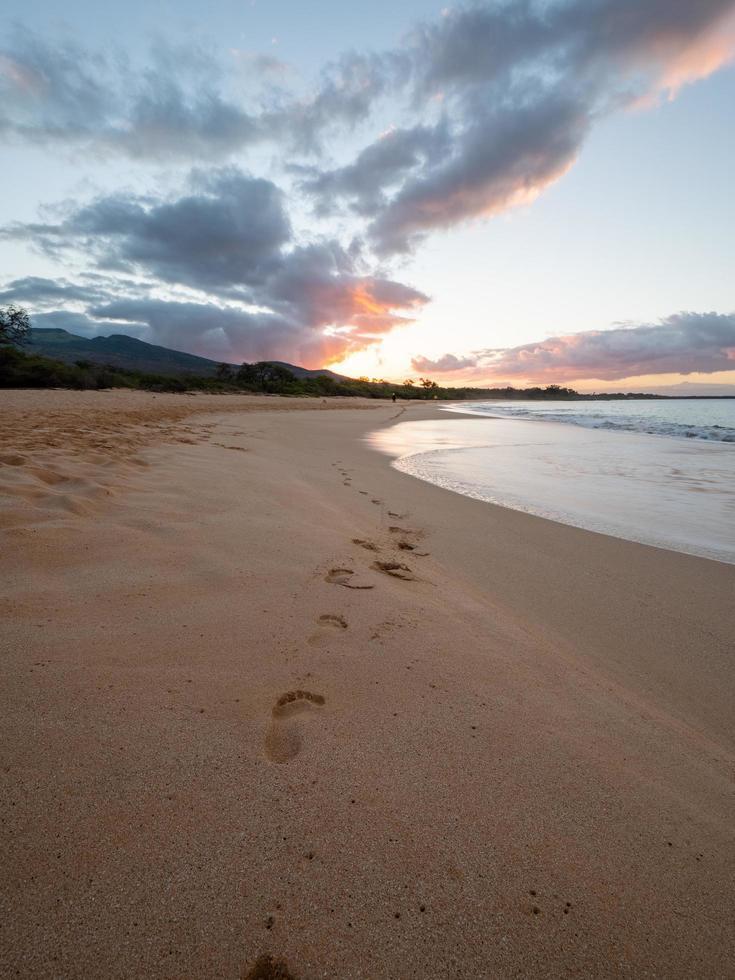 empreintes de pas sur la plage pendant le coucher du soleil photo