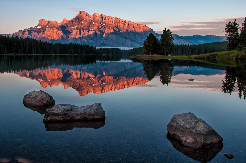 rochers dans l'eau près de la chaîne de montagnes au coucher du soleil photo