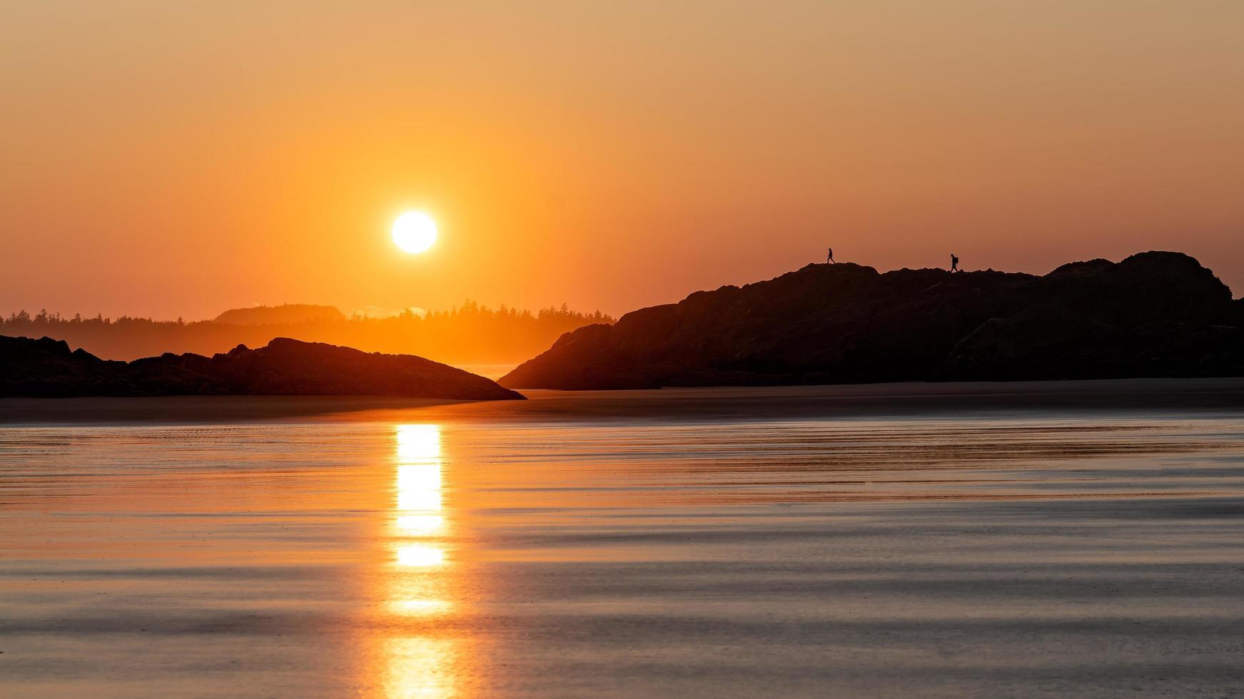 silhouettes de personnes marchant sur la côte rocheuse photo