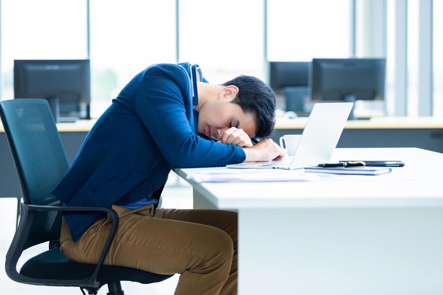 jeune homme d'affaires asiatique faisant une sieste au travail photo