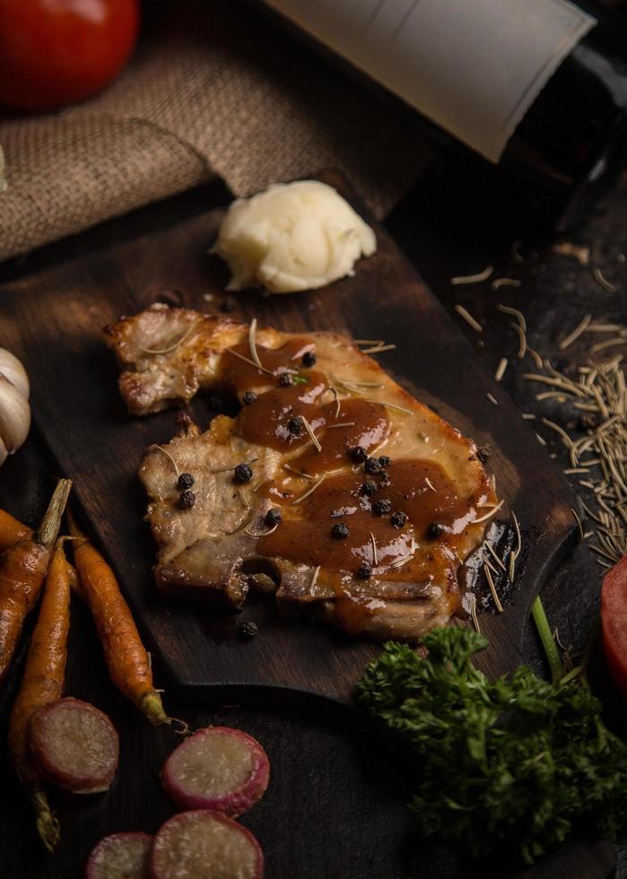 Steak de porc grillé sur une planche à découper photo