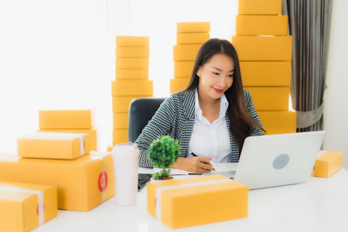 femme travaillant sur ordinateur portable avec des paquets autour d'elle photo