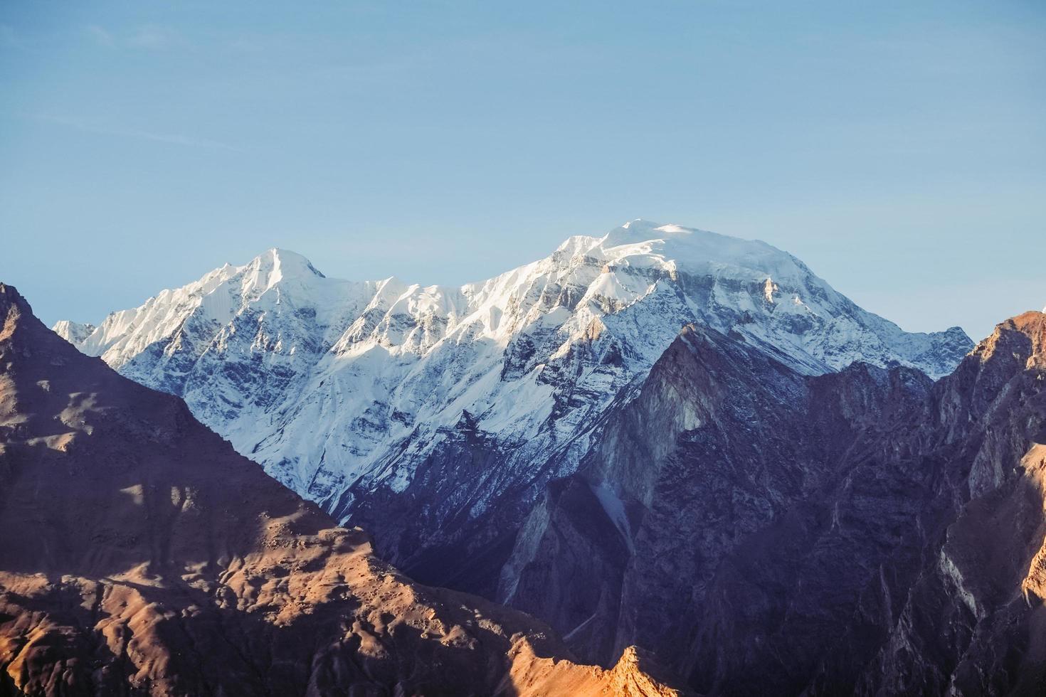 La lumière du soleil du matin brille sur la montagne enneigée photo