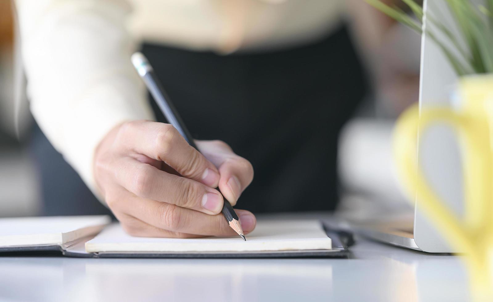 une main qui écrit sur un ordinateur portable avec un crayon photo