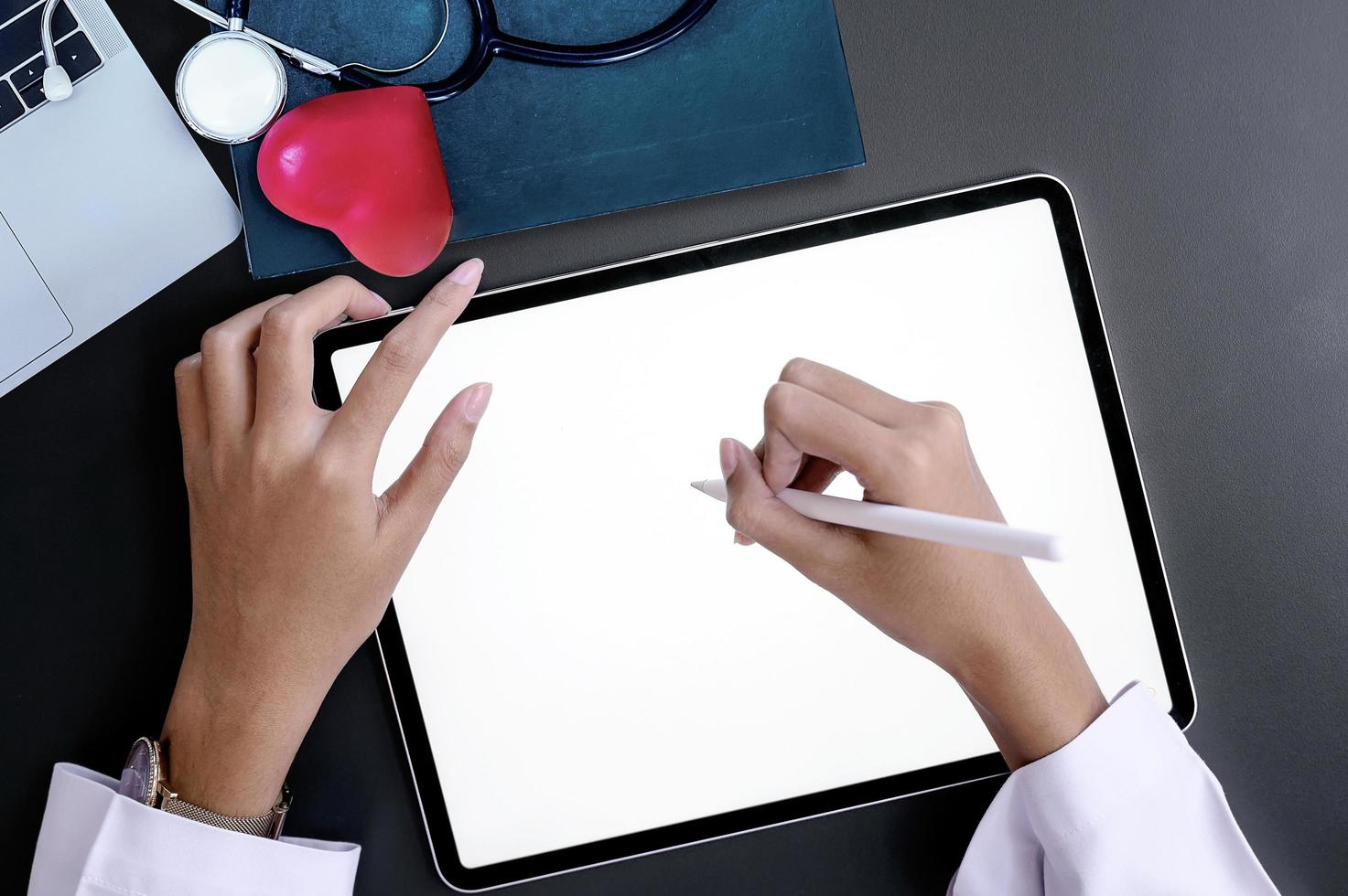 médecin main écrit sur l'écran de la tablette alors qu'il était assis au bureau. photo