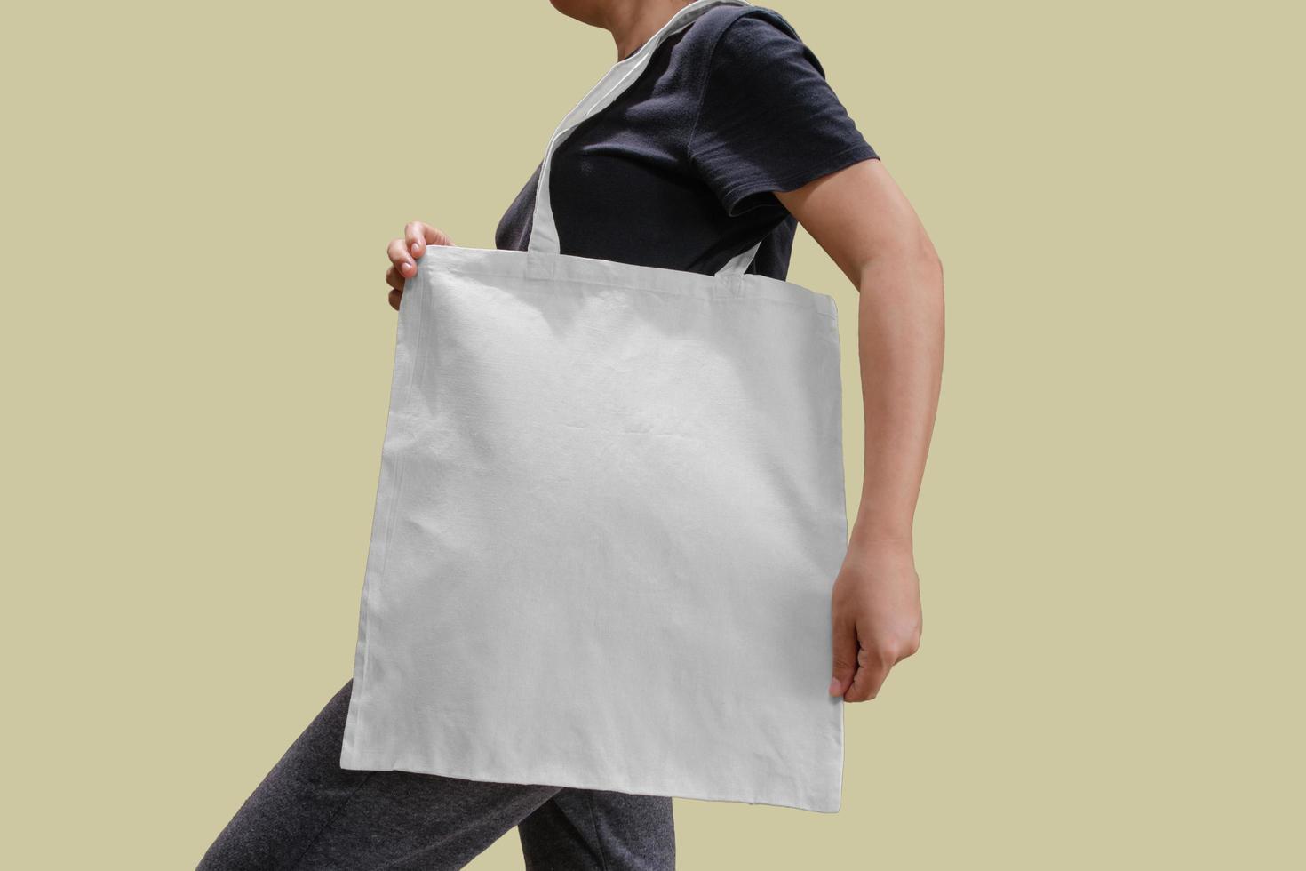 Femme tenant un sac fourre-tout en tissu pour maquette photo