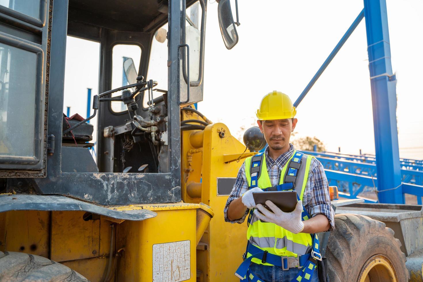 travailleur de la construction à côté de la chargeuse-pelleteuse photo