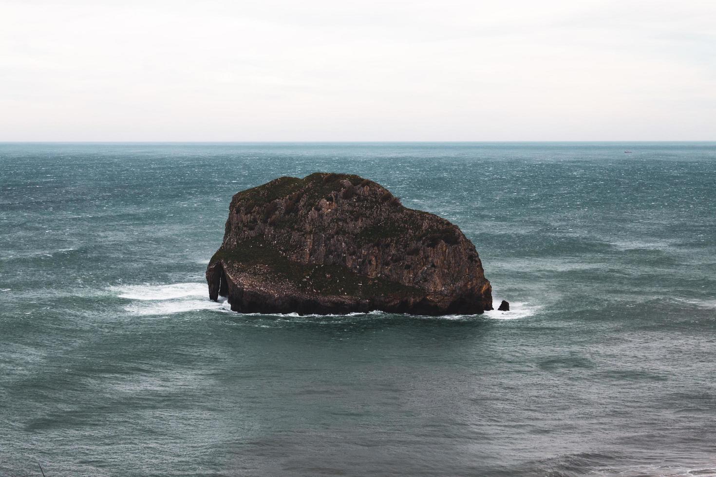 Formation rocheuse brune sur la mer sous un ciel blanc photo