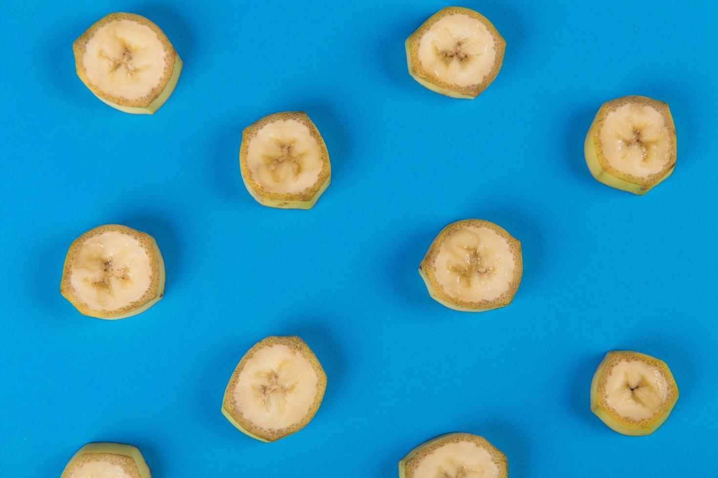 Tranches de banane non pelées sur fond bleu photo