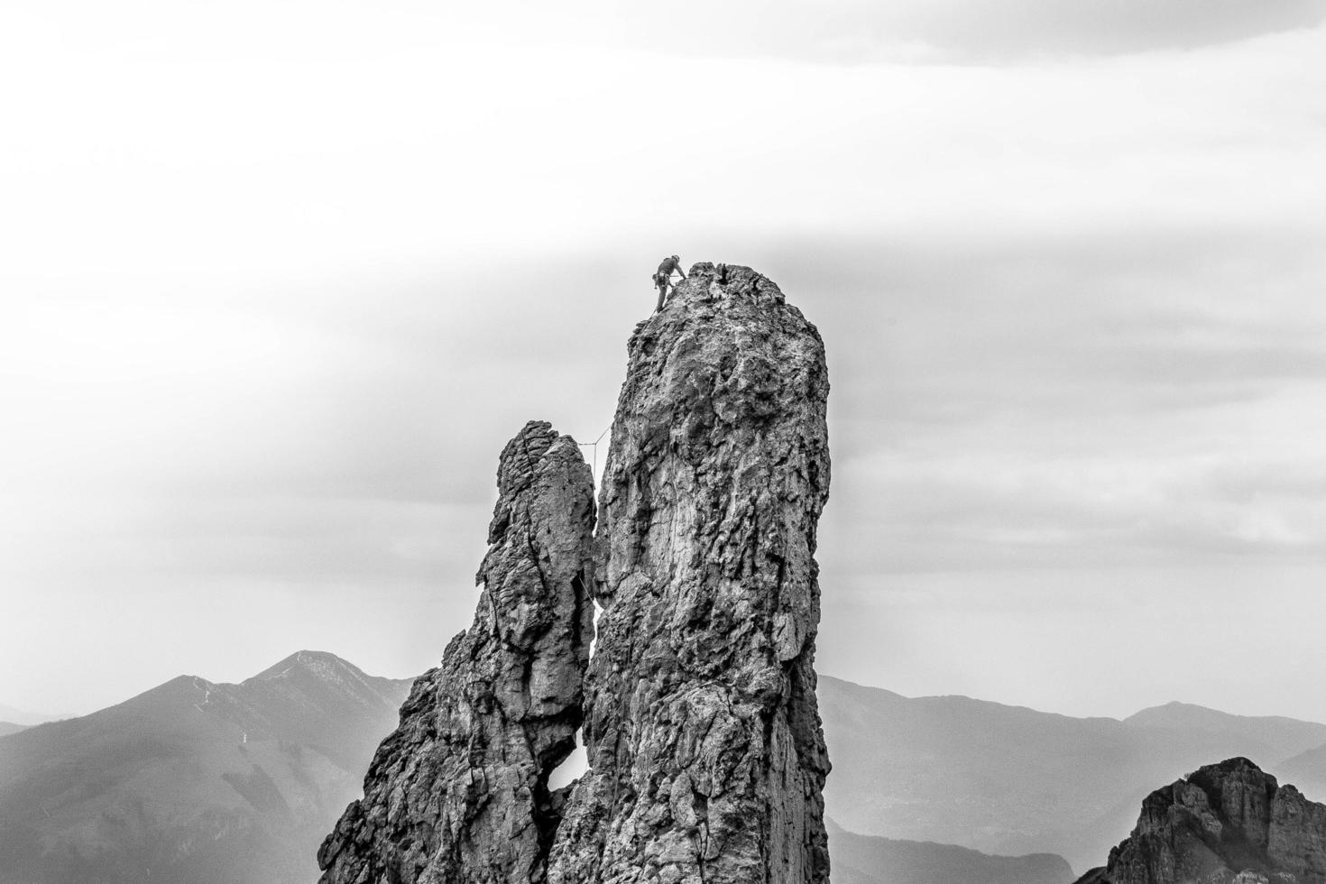niveaux de gris de la personne escalade la falaise photo