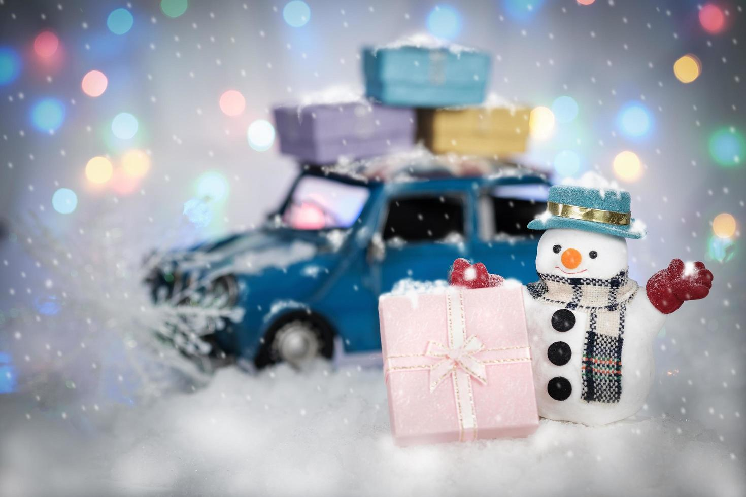 bonhomme de neige avec des cadeaux et une voiture photo