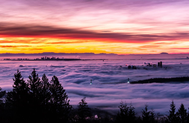 brouillard couvrant le pont et la ville au coucher du soleil photo