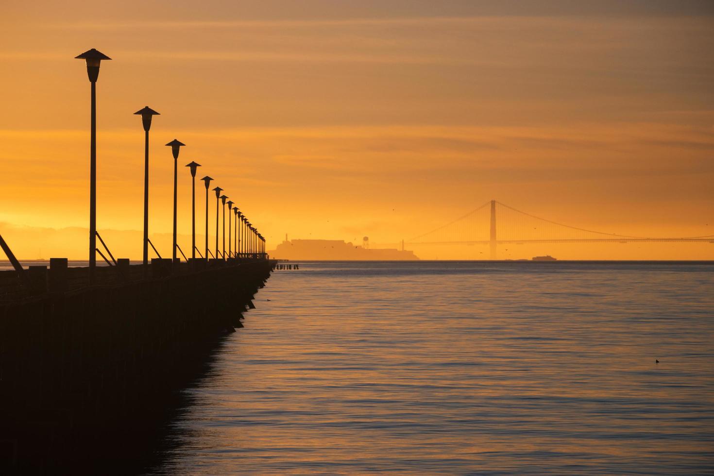 silhouette du pont au coucher du soleil photo