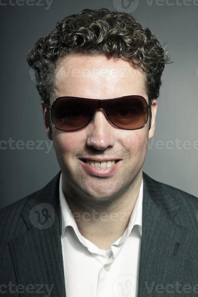 portrait en studio de l'homme d'affaires portant des lunettes de soleil sur fond gris. photo
