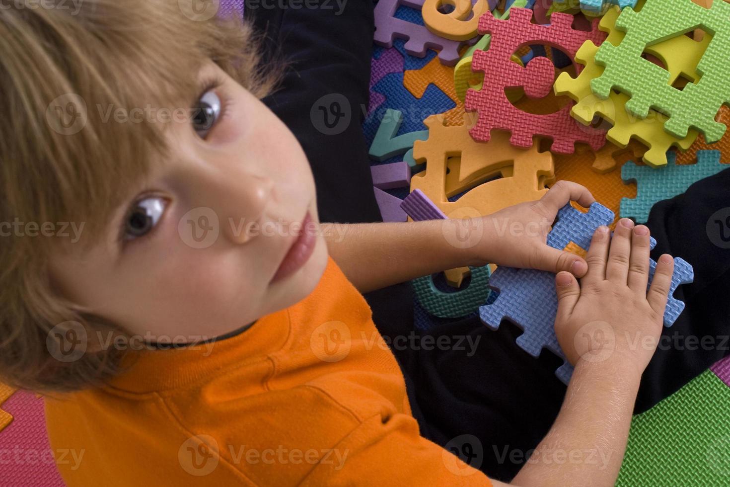 petit garçon joue avec des puzzles photo