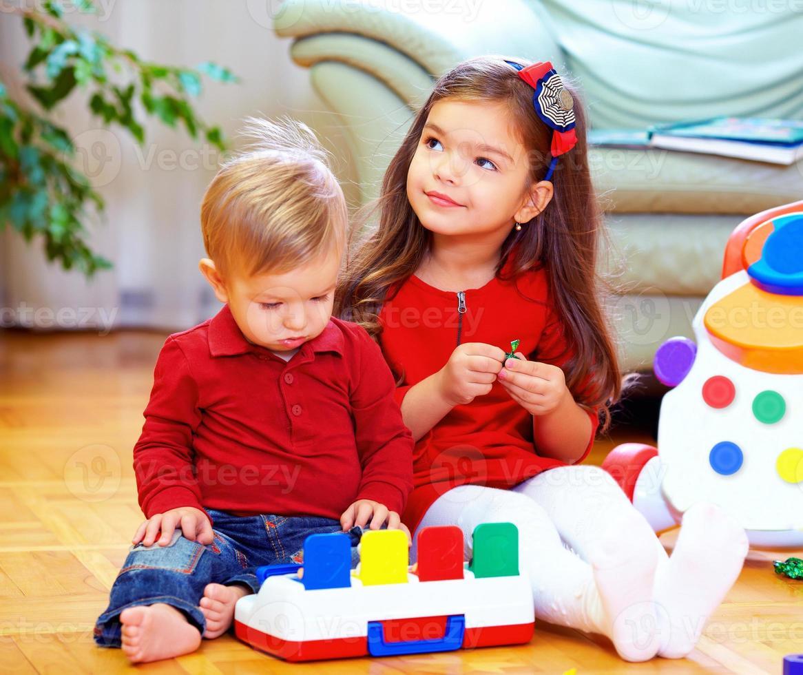 Bébés mignons jouant des jouets à la maison photo
