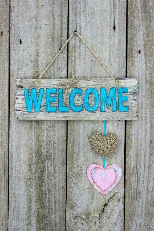 signe de bienvenue avec des coeurs suspendus sur fond de bois photo