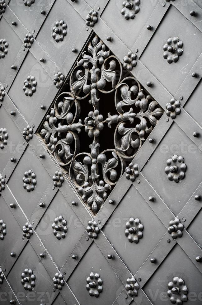 Ancienne porte en fer richement décorée avec grille photo