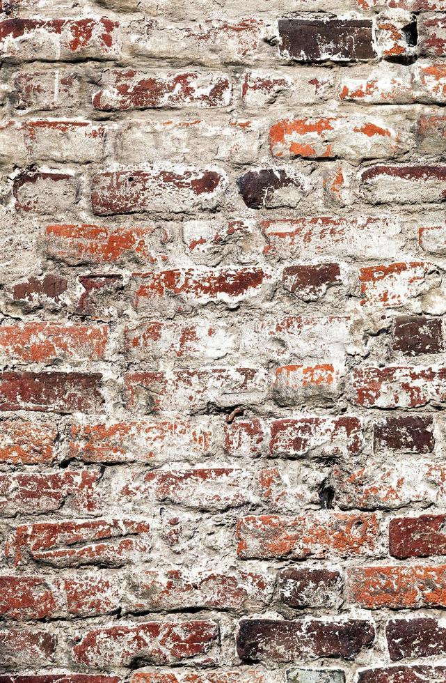 Vieux mur de briques minables blanchies à la chaux inégales pourries photo