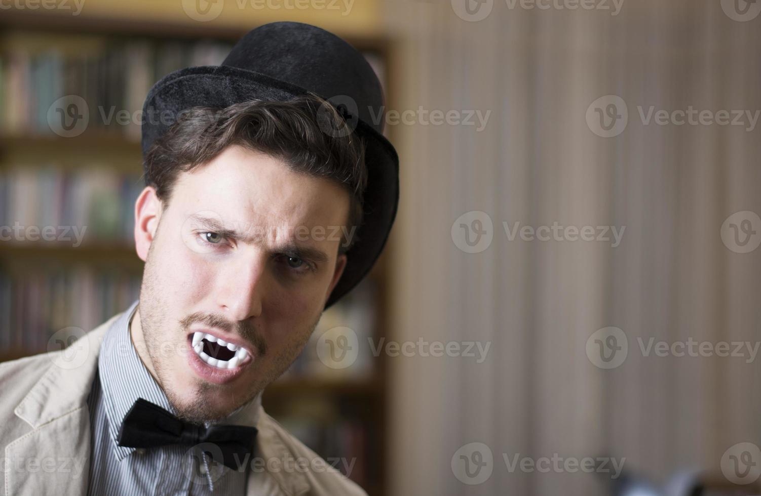 Gros plan jeune beau vampire blanc avec chapeau haut de forme noir photo