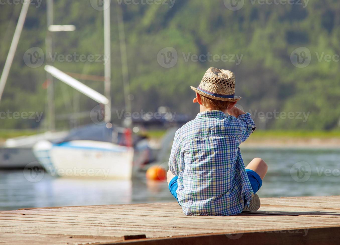 garçon sur la jetée en bois à la recherche d'un yahts photo
