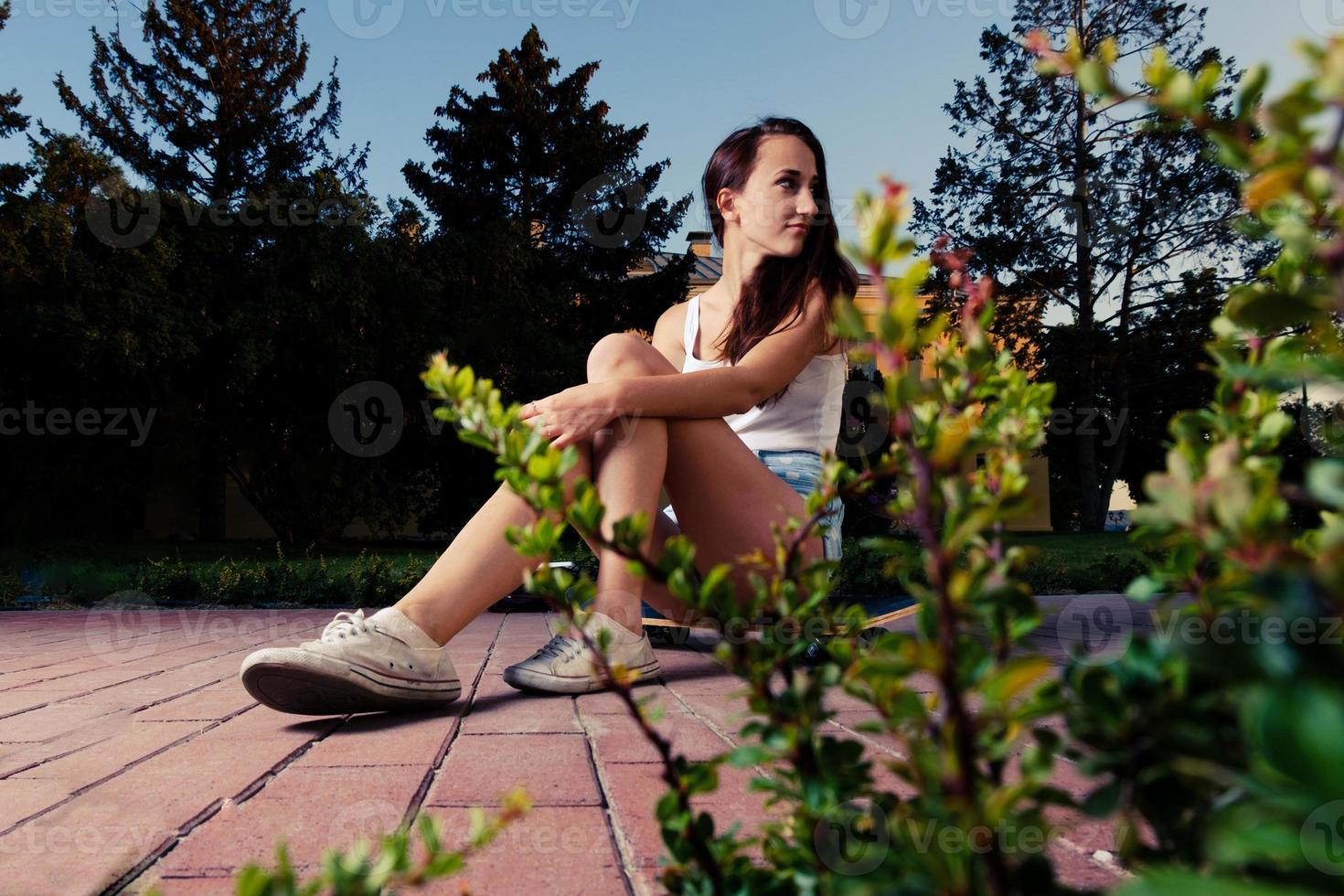 femmes assises sur une planche à roulettes regardant en arrière photo