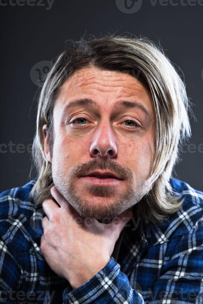 expressif jeune homme aux cheveux longs blonds et barbe. photo