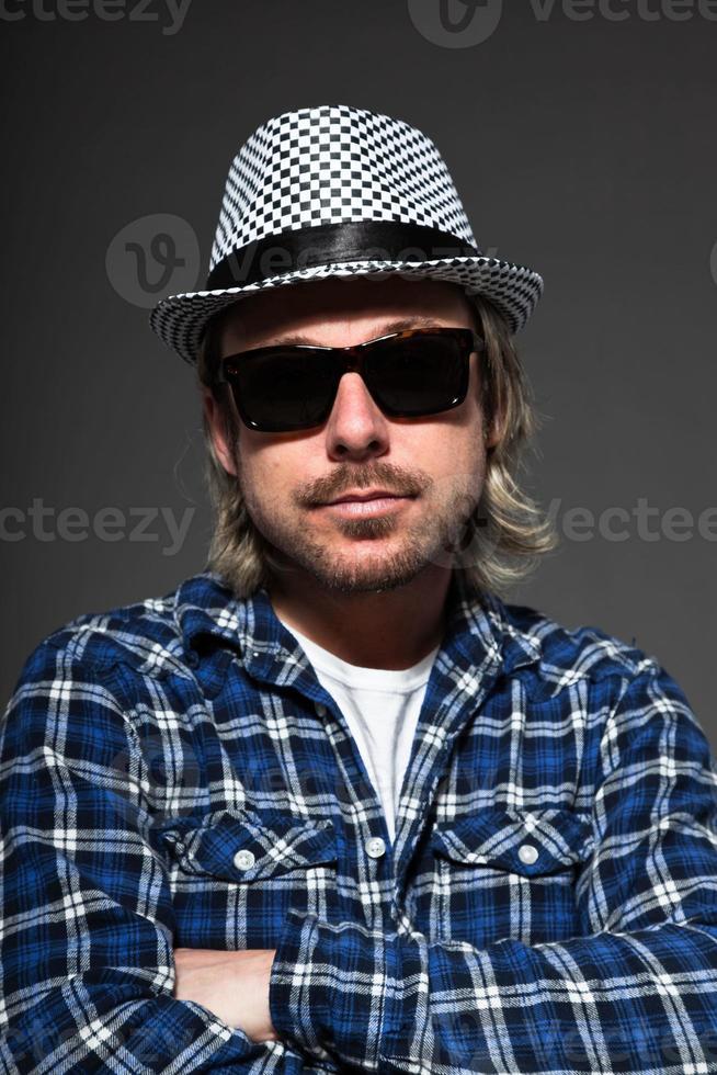 expressif jeune homme aux cheveux blonds portant chapeau et lunettes de soleil. photo